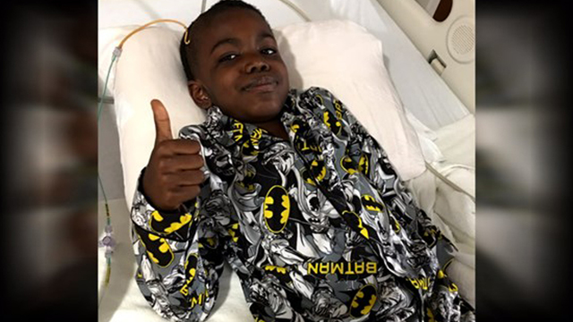 An 8-year-old boy celebrates after beating stage 4 brain cancer